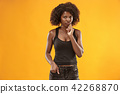 The serious business woman standing and looking at camera against gold background. 42268870