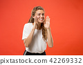 Isolated on pink young casual woman shouting at studio 42269332