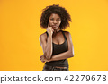The serious business woman standing and looking at camera against gold background. 42279678