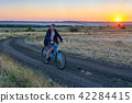 man ride a bike in the country field at sunset 42284415