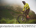 An adult mtb cyclist on a mountain bike at the foot of a cliff surrounded by green grass. Low clouds 42290552