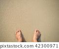 woman barefoot standing at a beach 42300971