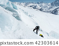 A professional mountaineer in a helmet and ski mask on the insurance does notch the ice ax in the 42303614