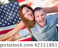 Military Couple Piggy Riding In Front of American Flag 42311801