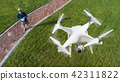Drone Quadcopter (UAV) In Air Above Pilot With Remote Controller 42311822