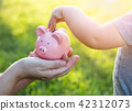 Woman Holds Piggy Bank While Baby Boy Puts Coins Inside 42312073