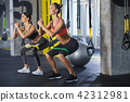 Grinning female couple is doing sit-ups in gym 42312981