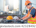 Engineer using drone and laptop for site survey 42328492