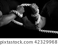 Men tighten a rope on a black background 42329968