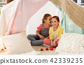 little girl playing tea party in kids tent at home 42339235