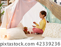little girl playing tea party in kids tent at home 42339236