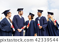happy students in mortar boards with diplomas 42339544