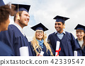 happy students in mortar boards with diplomas 42339547