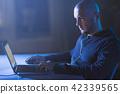 hacker in earphones typing on laptop in dark room 42339565