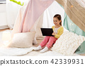 little girl with tablet pc in kids tent at home 42339931