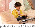 boy with pots playing music in kids tent at home 42339939