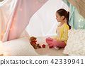 little girl playing tea party in kids tent at home 42339941