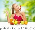woman with fruits and juice eating strawberry 42340012