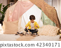 boy with pots playing music in kids tent at home 42340171