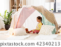 little girl playing tea party in kids tent at home 42340213