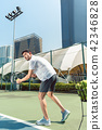 Young man playing tennis outdoors in a modern district of the city 42346828