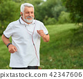 Positive running old man in green city park. 42347606