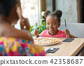 Happy, smiling girl can't wait to eating pizza with her mother. 42358687