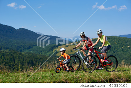 Family tourists bikers, mom, dad and child riding on bicycles on grassy hill 42359103