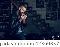 Young Bearded Biker Smoke Cigarette in Garage. 42360857