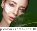 Beautiful fresh girl with cosmetic cream on the face, natural make-up and green leaves. Beauty face. 42361106