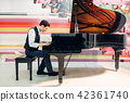 Male pianist practicing composition on grand piano 42361740