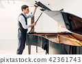 Male pianist opens the lid of black grand piano 42361743