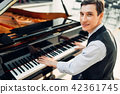 Male pianist poses at the black grand piano 42361745
