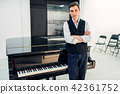 Male pianist stands at the black grand piano 42361752