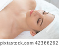 Relaxed young woman lying on spa bed for massage. 42366292