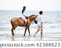 Young couple goes horse riding on tropical beach. 42366623