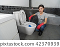 woman cleaning toilet bowl with brush 42370939
