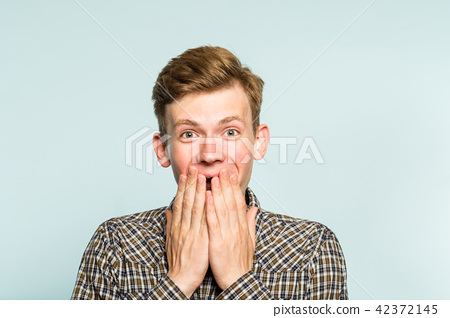 joyful excited happy man covering mouth emotion 42372145