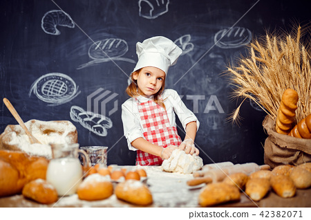 Adorable little girl in chef hat making dough 42382071