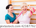 Physio assisting elderly woman during exercise with power band 42387762