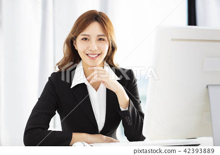 smiling young business woman working in office 42393889