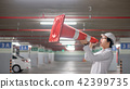 Asian engineer yelling though traffic safety cone 42399735