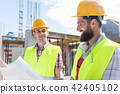 Two young construction workers analyzing together a plan 42405102