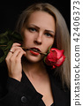 Passionate model with red rose in her mouth 42406373