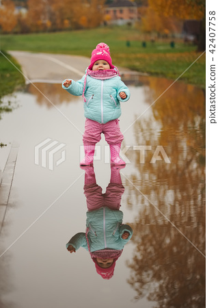 little girl with rubber boots in puddle 42407758