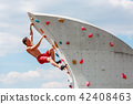 Photo of young sporty man in red shorts hanging on wall for rock climbing against blue sky with 42408463