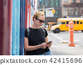 Woman using smartphones against colorful graffiti wall in New York city, USA. 42415696