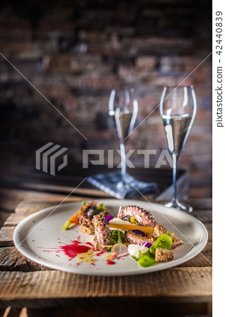 Octopus with vegetable salad on white plate. 42440839