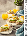 Sandwich with avocado and fried eggs 42444038