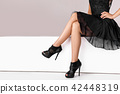 legs woman wearing high heels shoes sitting on bench. 42448319